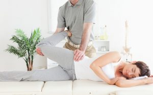 Chiropractor making adjustments on lady.